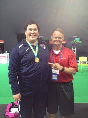 Sara Robles poses with Dr. Mark Lavallee after winning gold at a pre-Olympics weightlifting competition in Rio de Janeiro.