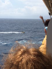 Passengers on the Disney Fantasy wave to three Cuban refugees clinging to a capsized boat.