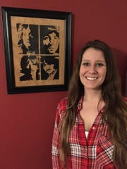 Stacey Ginsbach is shown next to a wood cutout of The Beatles that she has displayed in her Yankton home.