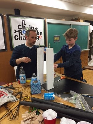 A parent and child create a Rube Goldberg machine as part of the Chain Reaction Challenge.