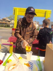 Jackson Goldapske, 10, of North Fond du Lac, hand-squeezes lemons for each glass of lemonade sold on Saturday during Fond du Lac's Lemonade Day.