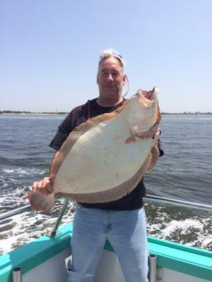 Dave McDermott holds fluke of over 11 pounds he caught on the Atlantic Star party boat.