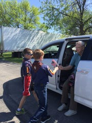 Bob Schneider gives out flags at this year's Memorial Day parade in Kewaunee.