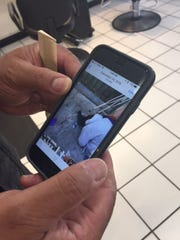 Paul Mediano, owner of Heads Up Hair Designs, shows a picture he took of a man slumped over near his business. Next to the man is a syringe.