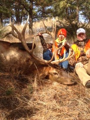 Andrew Almos, left, shot this bull elk while hunting with his brother Luke and father Travis.