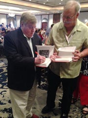 """Dick Morris signs a copy of his book """"Armageddon"""" for a member of the Florida delegation to the Republican National Convention on Wednesday, July 20, 2016."""