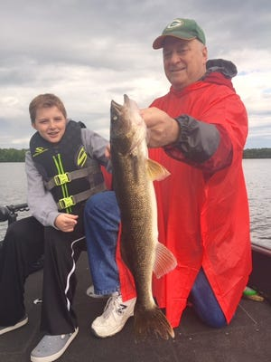 Jude and Bill Adams behind a big walleye.