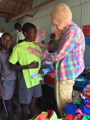 Sidney Bonvallet of Farmington Hills helps a youngster in Zimbabwe get the correct size T-shirt. Bonvallet and other members of her organization, Helping Hands, Touching Hearts, was in Africa from March-May. They'll return with more donations next year.