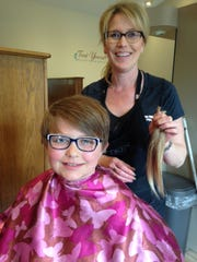 Pictured is Madison Cornell getting her hair cut with