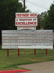 """""""A tradition of excellence,"""" boasts the billboard for Treynor High School Cardinals."""