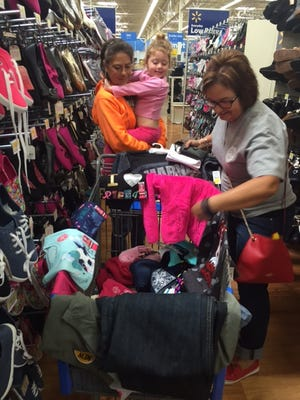 Ginger Antrican of the Mansfield Police Athletic League, at right, assists Hester Lacy shop for her two grandchildren, including Kayelynn Sapp, 3, during the annual Kops 'N Kids program Sunday at Walmart on O'Possum Run Road.