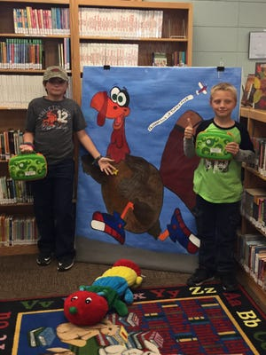 """Marion County Library patrons Isaiah Albrecht (right) and Dylan Blair recently """"dropped by"""" the library to see how the preparations for Turkey Trot were coming along. They ran into Fowler the Feathered Friend and Abby the Bookworm and decided to take advantage of the LeapFrog tablets that are now available for young patrons to enjoy while they visit the library. Everyone is invited to drop in and have a photo-op with Fowler and Abby. For information about upcoming events at MCL, call (870) 449-6015, or log on to www.marcolibrary.org."""