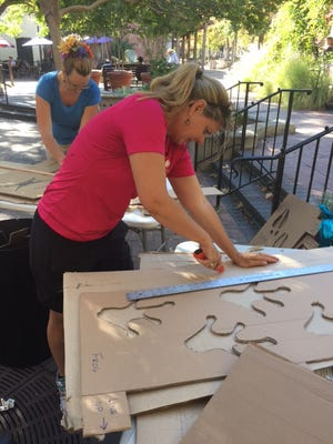 Erin Hansen, foreground, and Susan Evergreen Hericks work on stencils for frog prints that will be part of the Ojai Day mandala. The giant circle of art will be washed away at the close of Saturday's daylong festival.