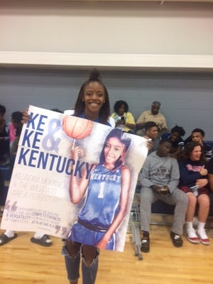 Fulton High girls basketball standout KeKe McKinney displays a Kentucky poster after announcing her choice of the Wildcats.