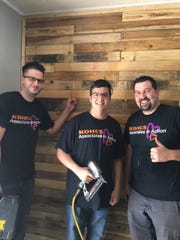 Paul, Lazaro and Nick stand by the completed pallet wall.