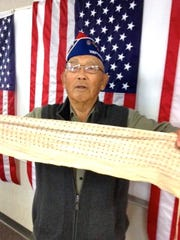 Robert Yano displays a Senin Bari, a cloth belt he wore around his waist to keep him safe.