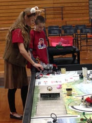 Alyssa Hagan, dressed as a deer, works with Lego League team member Johnny Thompson on the robot portion of competition.