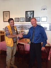 Abilene Founders Lions Club president Jeff Eckard presents a donation to Brian Massey, director of Houses for Healing.