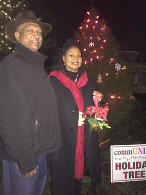 Shonda Johnston, a Wallace Intermediate School teacher who suggested the CommUNITY tree idea to Main Street Vineland, and her husband, Reginald Johnston, a member of the Main Street Vineland Board of Directors, prepare to place their ornament on the CommUNITY tree during the tree decorating party.