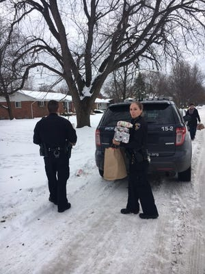 Officer Caitlin King holds gifts as police officers arrive to help a local family for Christmas.