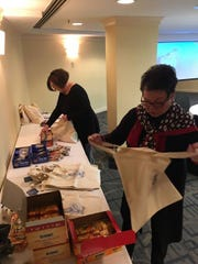 Paula Manalokos and Cathy Watts stuffing welcome bags for the Delaware delegation attending the inauguration of Donald Trump.