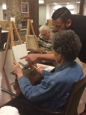 Andres Gonzales assists Helen Merrick, a resident of Baptist Retirement, with painting techniques during one of the regularly scheduled art classes at Baptist Retirement Community.