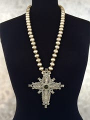 A silver cross with mercury dime beads by precious
