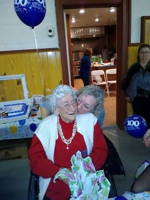 Dolcie Godwin, left, gets a kiss from her daughter, Brenda Carey, at her 100th birthday celebration at the Saxis FIrehouse on Saxis, Virginia on Saturday, Feb. 11, 2017.