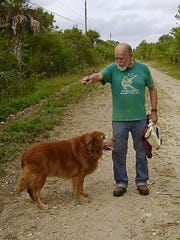 Bob Gore plays with his beloved golden retriever Cailin in 2009 on the road leading to Gore's Naithloriendun Wildlife Sanctuary in rural Collier County.
