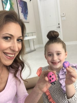 Mom Lauren Morgenstern, left, and Ayel Morgenstern, 6, of Parkland, Florida, with some of the stones Ayel painted for vandalized Jewish cemeteries.