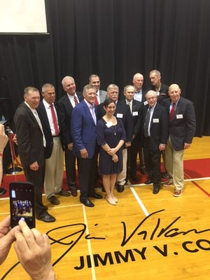 Members of Rutgers' 1967 men's basketball team pose with Lee Ann Valvano at court naming ceremony for Jim Valvano