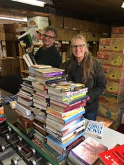 "Alan Cresswell, left, and Katy Clay sort books for the Friends of Legal Services Book Sale in the ""book nook,"" the location where books and other items for the sale are stored, sorted, prices and boxed up."