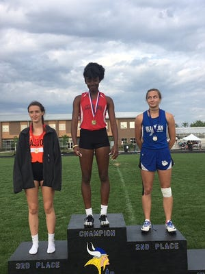 Ashley Woolfork stands in the center of the podium after her victory in the 400-meter race.