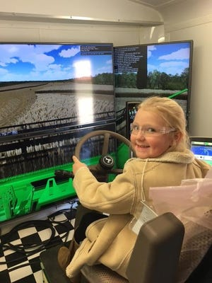 Maddie Houston learns farming techniques in simulator provided by Hutson Inc. of Hopkinsville.