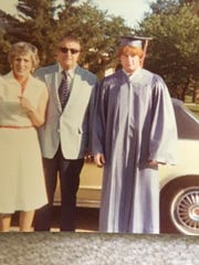 Russ Ball poses with his parents at high school graduation.