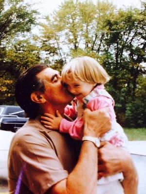 Vernon Houchen holds his granddaughter, Annie McMahon, in 1984.