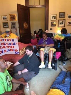 People gather in Senate Majority Leader Mitch McConnell's office in Washington on Thursday to protest Republicans' version of healthcare legislation to repeal and replace Obamacare.