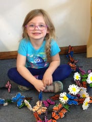 "Norah sits among some butterfly manipulatives ""under"