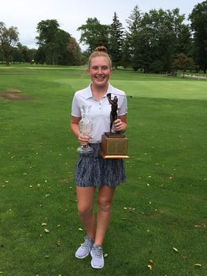 Sarah Willis of Eaton holds the Kay Wigton crystal trophy and the Marion Country Club trophy with names of all the winners of the Ohio Junior Girls Championship since it started in 1977. Willis shot a 106 over 27 holes to win by a stroke on Tuesday.