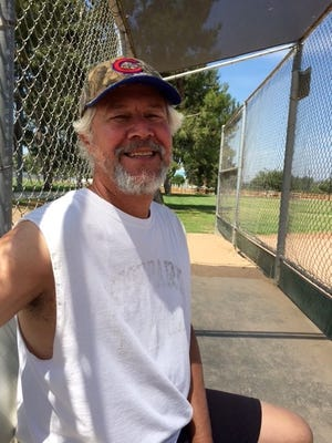 Dan Burchfield takes a short rest in the dugout at Arroyo Vista Park in Moorpark. The Moorpark High teacher is training to walk 100 miles later this month to raise money for scholarships to honor his son, Joel, who drowned in 1996.