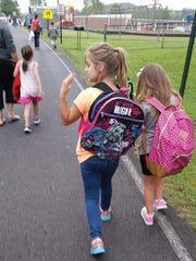 Children and parents walk along Old Franklin Road on