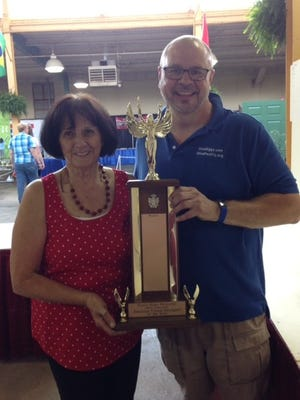 Mary Lee Minor (L)  member of the Earth, Wind and Flowers Garden Club, was presented the first-ever  Dottie Bates Memorial trophy for her floral designing through three Ohio State Fair flower shows. Jim Chakeres (R) presented the award.