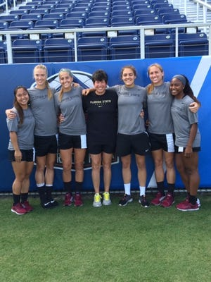 Florida State Director of Sports Medicine Robin Gibson poses with members of the FSU soccer team.