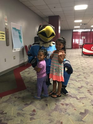 Pensacola Ice Flyers mascot Maverick joins with two young girls whose family evacuated from Hurricane Irma and sought shelter at Pensacola Bay Center.