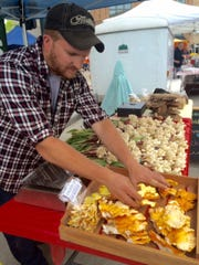 Mushroom hunter Kevin Olson of Rhinelander sets out the fungal delicacies earlier this year that he forages from Wisconsin woods, like wild leeks and chicken of the woods. He is one of 140 vendors selling their wares each week at the Oshkosh Saturday Farmers Market.