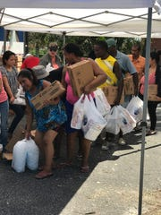 People pick up food, water and other supplies at a