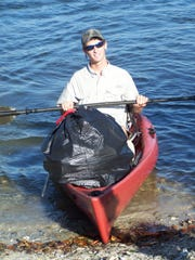 A kayaker brings in a full trash bag during a marine cleanup with Keep Lee County Beautiful.