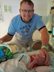 Ty Krean strokes the head of his infant son, who was born prematurely at 24 weeks.