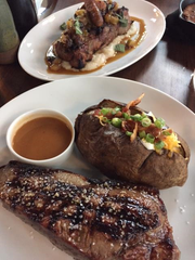 Dishes at The Walnut Kitchen in Maryville include, front, a 14-ounce strip steak that comes with a small ramekin of gravy, a loaded baked potato and, back, cider-brined pork tenderloin, served with Shelton Farm grits, andouille sausage and stewed apples.