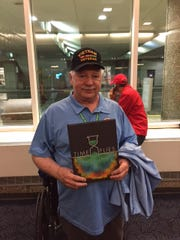 Veteran Spencer Smith stands with the copy of the Nathan Hale High School yearbook he received during his Honor Flight.